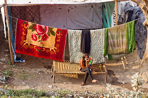 bedding on cloth line (india), bedding, blankets, comforters, girl, hanging, house, peoplecloth line, sitting, village
