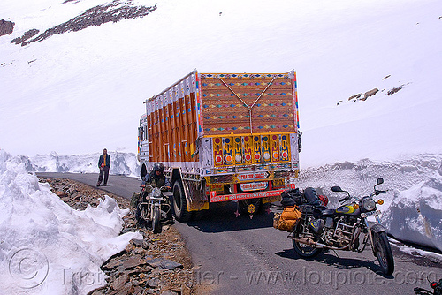 ben driving his motorcycle around a stalled truck - manali to leh road (india), baralacha pass, baralachala, ben, ladakh, lorry, motorbike touring, motorcycle touring, mountain pass, mountains, rider, riding, road, royal enfield bullet, snow, truck