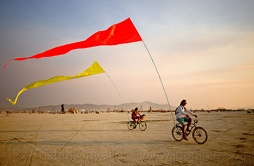 bicycles flags - burning man 2013, bicycle flags, bicycles, burning man, couple, poles, red, riding, streamer flags, streamers, two, yellow