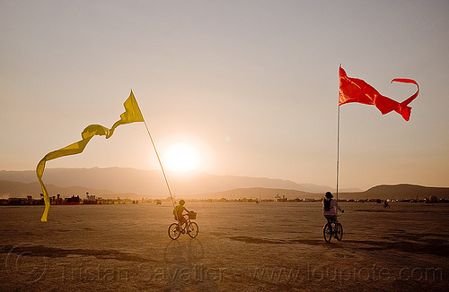 bicycles with streamer flags - burning man 2013, bicycle flags, bicycles, burning man, couple, poles, red, riding, streamer flags, streamers, sunset, two, yellow