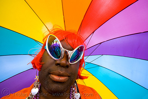 black drag queen with rainbow umbrella, african american man, alien sunglasses, black man, crossdressing, drag queen, earrings, gay pride 2008, gay pride festival, guy, rainbow colors, red wig, sf gay pride, transvestite, umbrella