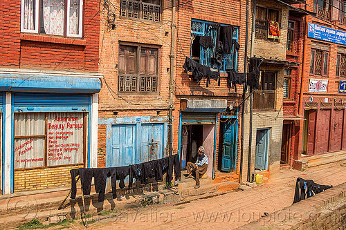 black dyed clothing drying on lines in street (nepal), bhaktapur, cloth line, drying, dyed, houses, man, sitting