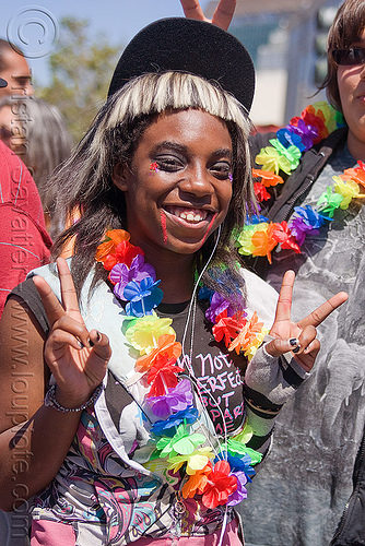 black teen girl at the san francisco gay pride, black woman, flower necklace, gay pride festival, girl, peace sign, rainbow colors, rainbow necklace, v sign