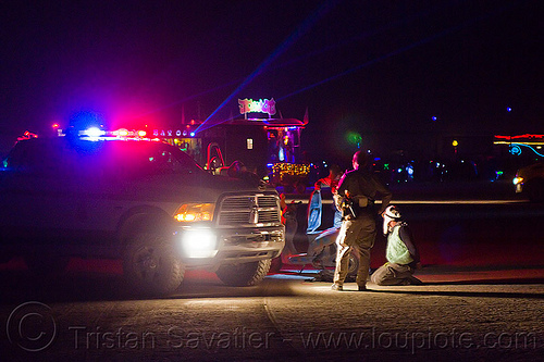 BLM rangers arrest a man riding a scooter - burning man 2012, arresting, blm rangers, burning man, law enforcement, leo, lorry, motorcycle, night, officers, police action, police arrest, police lights, suv, truck, under arrest