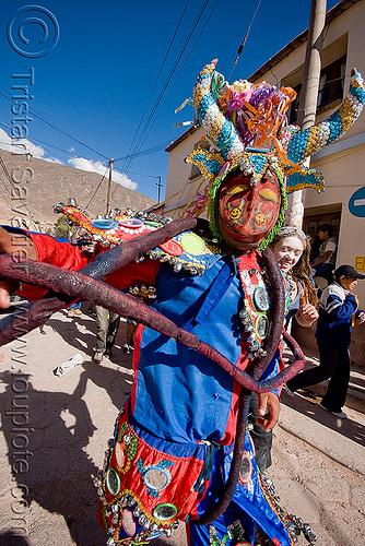 blue diablo carnavalero holding his tail - carnaval - tilcara (argentina), andean carnival, careta, careta de diablo, confettis, costume, diablo de carnaval, folklore, horns, indigenous, indigenous culture, man, mask, mirrors, noroeste argentino, people, quebrada de humahuaca, serpentine throws, tribal