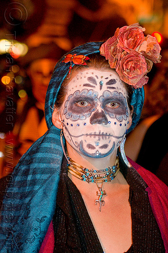 blue sugar skull makeup, blue head cover, blue necklace, day of the dead, dia de los muertos, dry flowers headdress, face painting, facepaint, flower headdress, gecko necklace, halloween, headcover, lizard necklace, night, orange dragonfly jewelry, orange flowers, sugar skull makeup, woman