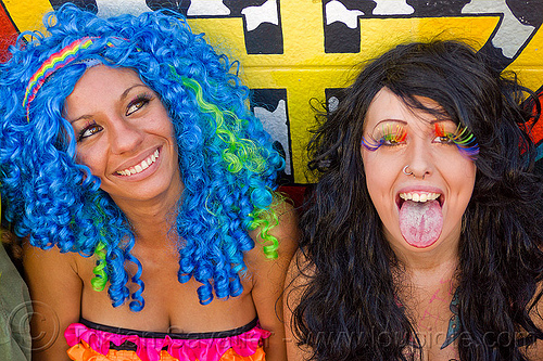 blue wig - rainbow eyelashes, blue wig, fake eyelashes, gay pride festival, nose piercing, nose ring, nostril piercing, party eyelashes, party fashion, rainbow eyelashes, rainbow headband, rave fashion, revelers, sticking out tongue, sticking tongue out, two, women