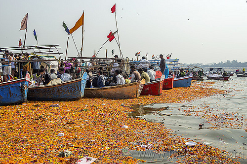 boats and flower offerings on the ganges river, colorful, flags, floating, flower offerings, ganga, ganges river, hindu pilgrimage, hinduism, india, maha kumbh mela, orange flowers, paush purnima, pilgrims, river boats, triveni sangam