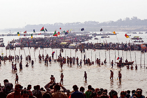 boats and hindu pilgrim bathing in the ganges river at sangam - kumbh mela 2013 (india), backlight, colored flags, crowd, dawn, fence, ganga river, ganges river, hindu, hinduism, holy bath, holy dip, kumbha mela, maha kumbh mela, paush purnima, pilgrims, ritual bath, river bath, river bathing, river boats, silhouettes, triveni sangam, water, yatris