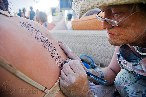 body painting at the center camp cafe - burning man 2009, artist, body art, body paint, body painting, burning man, damien, drawing, hyeroglyphs, skin, symbols, writing