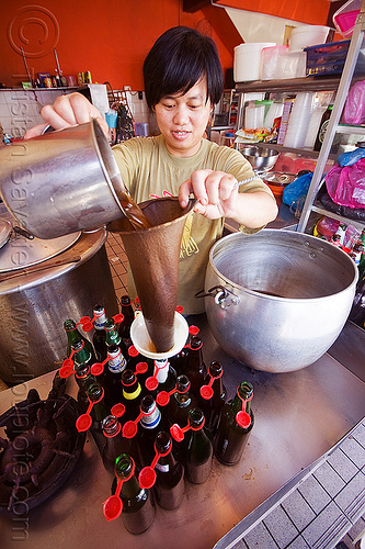 brewing a local concoction, botteling, bottles, drink, home-made, infused, infusion, man, miri, pots, sift, sifting