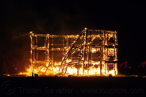 the burning frame unrolls and collapses - burning man 2012, backlight, building, burning, collapsing, fire, flames, night, silhouettes, the man, wood frame, wooden frame