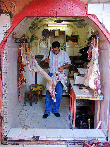 butcher in meat shop, butcher knife, carcass, carcasses, chevon, cleaver, cutting, goat, halal, halal meat, hanging, hooks, kurdistan, man, mardin, meat market, mutton, people, raw, raw meat, worker