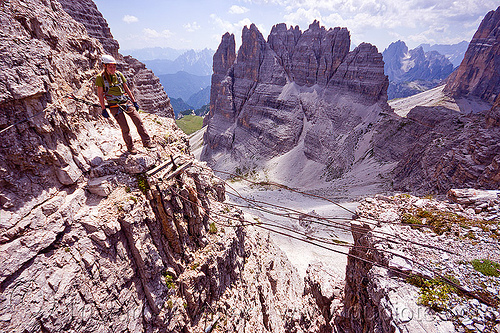 cable foot bridge - monte paterno via ferrata, alps, cables, chasm, cliffs, climber, climbing harness, climbing helmet, dolomites, footbridge, monte paterno, mountain climbing, mountaineer, mountaineering, mountains, parco naturale dolomiti di sesto, rock climbing, shaky bridge, via ferrata, woman