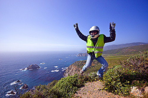 california coast near big sur, big sur, california coast, carmel, cliff, gloves, islets, jump shot, leather jacket, monterrey, motorbike helmet, motorcycle helmet, pacific ocean, refective jacket, rocks, safety jacket, sea, seashore, sharon, shore, sunglasses, trail, woman