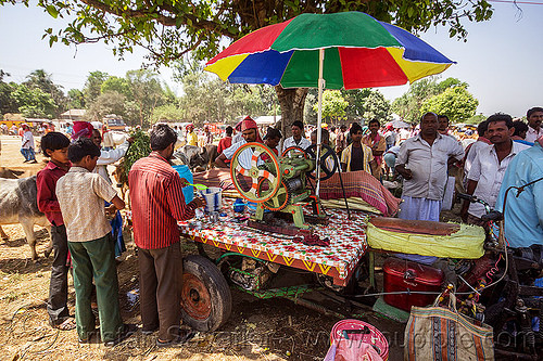 cane juice machine (india), crowd, men, people, press, rainbow colors, stand, street food, street vendor, sugar cane, umbrella, west bengal