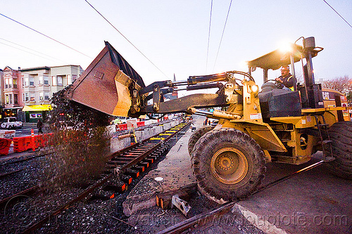 caterpillar CAT IT38G wheel loader drops ballast on rail tracks, ballast, cat it38g, front loader, gravel, high-visibility jacket, high-visibility vest, light rail, man, muni, ntk, overhead lines, railroad construction, railroad tracks, railway tracks, reflective jacket, reflective vest, safety helmet, safety vest, san francisco municipal railway, track maintenance, track work, wheel loader, wheled loader, workers