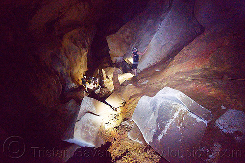 cavers scrambling around big blocks - clearwater cave - mulu (borneo), blocks, cavers, caving, clearwater cave system, clearwater connection, gunung mulu national park, knotted rope, natural cave, spelunkers, spelunking