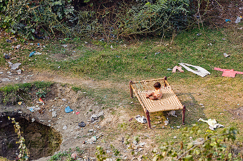child sitting on a bed frame in a field, bed, child, cloth, drying, environment, garbage, india, kid, plastic trash, pollution, single-use plastics, sink hole, sitting, toddler