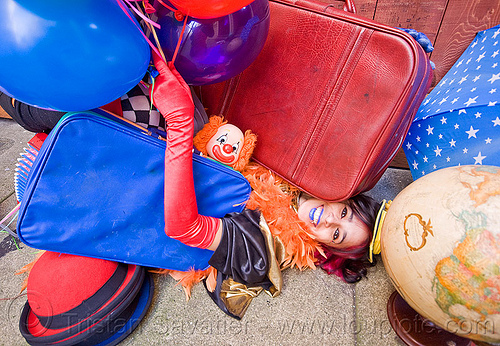 clown act, blue lipstick, bowler hat, circus artist, clown, feather boa, globe, luggage, mumu, party balloons, performer, props, suitcases, woman
