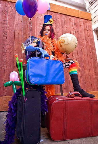 clown act - mumu circus performer, blue lipstick, circus artist, clown hat, cocktail hat, feather boa, globe, luggage, party balloons, performer, props, suitcases, woman