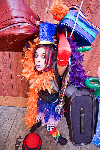 clown act, blue lipstick, bowler hat, circus artist, clown hat, cocktail hat, feather boa, globe, luggage, mumu, party balloons, performer, props, suitcases, woman