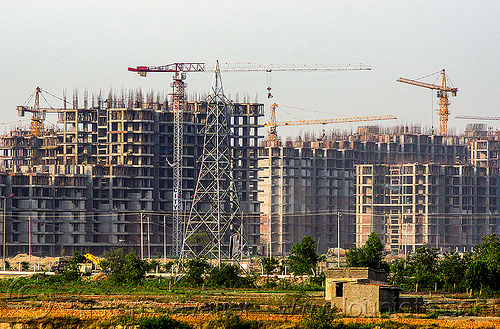 "construction of the planned urban development ""gaur city 1"" in greater noida (india), bamboo scaffoldings, building construction, buildings, construction cranes, electricity pylon, gaur city, greater noida, planned city, transmission tower, urban development, urban planning"