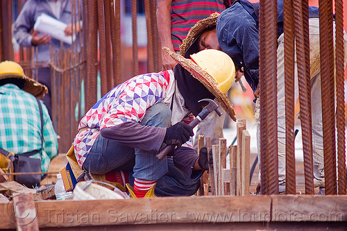 construction worker building concrete formwork, borneo, building construction, concrete forms, concrete wall forms, construction site, construction workers, face mask, formwork, hammer, lumber, malaysia, man, miri, rebars, safety helmet, squating, straw hat, sun hat, timber, working