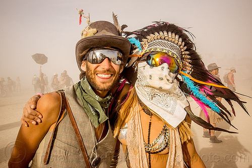 couple during white out - burning man 2015, bandana, burning man, couple, dust storm, feather headdress, feathers, mathieu, mirror sunglasses, pia, white out, windy, woman