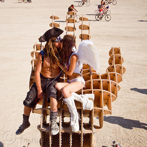 couple kissing on hands sculpture - burning man 2013, angel, art installation, burning man, couple, david gerler, hands sculpture, kissing, making out, pirate, sitting, woman, wooden frame
