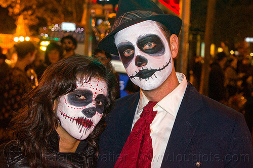 couple with skull makeup, day of the dead, dia de los muertos, face painting, facepaint, halloween, hat, man, night, red spots, red tie, skull makeup, white shirt, woman