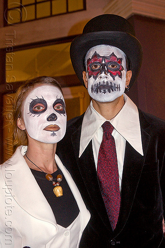 couple with skull makeup, day of the dead, dia de los muertos, face painting, facepaint, halloween, man, necklace, night, red tie, shirt collar, stovepipe hat, sugar skull makeup, suit, woman