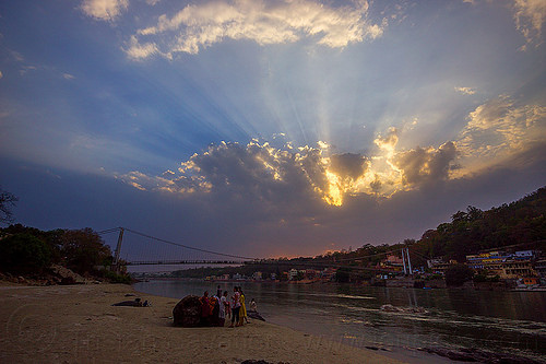 crepuscular rays at sunset on ganges river in rishikesh (india), beach, cloudy, crepuscular rays, ganga, ganges river, india, ram jhula, rishikesh, sun rays through clouds, sunset, suspension bridge