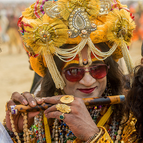drag queen hindu guru playing flute - kumbh mela (india), beads, costume, decorated, dressed-up, finger rings, flute, guru, headdress, hindu pilgrimage, hinduism, india, maha kumbh mela, makeup, man, necklaces, sunglasses, tilak, turban