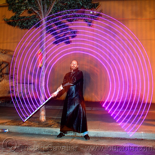 duane with LED-light saber - superhero street fair (san francisco), concentric circles, duane, islais creek promenade, led-light saber, man, night, shiftbrite, superhero street fair