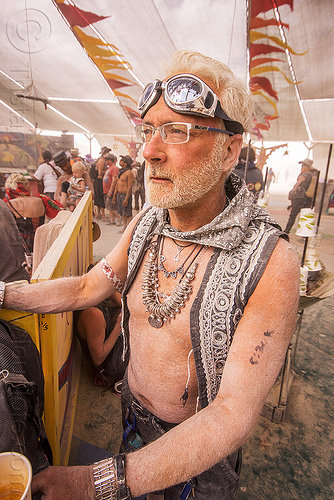 dusty man gazing at center camp - burning man 2015, burning man, center camp, dusty, goggles, metal necklace, prescription glasses, spectacles, white hair