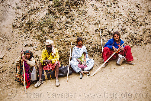 exhausted and dusty family resting on trail - amarnath yatra (pilgrimage) - kashmir, amarnath yatra, hiking canes, hindu pilgrimage, india, kashmir, mountain trail, mountains, pilgrims, resting, trekking, walking sticks