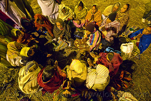 family of hindu devotees praying in a circle (india), ceremony, family, hindu pilgrimage, hinduism, india, maha kumbh mela, men, offerings, paush purnima, pilgrims, praying circle, ritual, sitting, straw, women