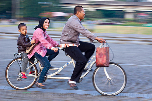family riding tandem bicycle, bike, boy, child, couple, jakarta, java, kid, man, medan merdeka, merdeka square, moving, park, people, road, street, tandem bike, woman