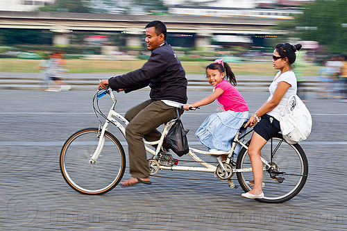 family riding tandem2 - family on tandem, child, family, jakarta, kid, little girl, man, medan merdeka, merdeka square, moving, park, riding, road, tandem bicycle, tandem bike, woman