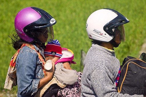 feeding baby bottle on motorbike, baby bottle, bottle feeding, helmets, indonesia, jogja, man, mother, motorcycle helmet, rider, riding, woman, yogyakarta