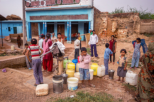filling up plastic water containers at village hand pump (india), blue house, children, crowd, hand pump, india, khoaja phool, kids, plastic jugs, pumping, village, water jugs, water pump, खोअजा फूल