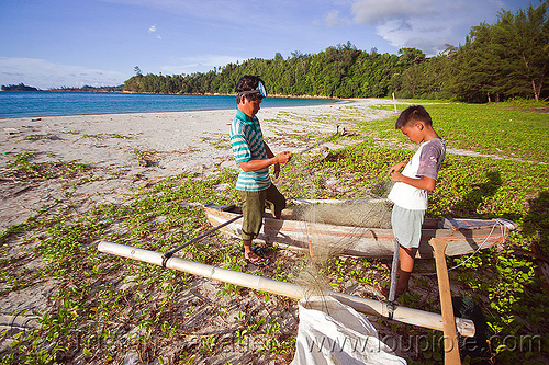 fishermen checking their fishing net, bangka, borneo, boy, climbing plants, creeper plants, double outrigger canoe, fisherman, fishermen, fishing canoe, fishing net, kelambu beach, malaysia, man, river boat, rowing boat, sand, seashore, small boat