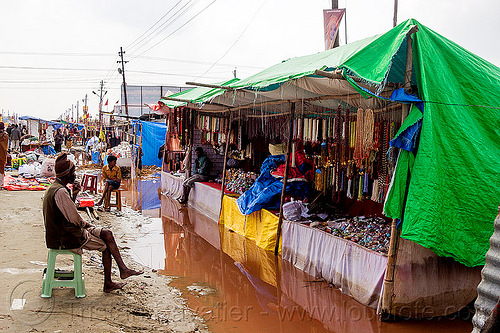 flooded market stalls - kumbh mela 2013 (india), flood, flooded, hindu, hinduism, kumbha mela, maha kumbh mela, man, merchant, shopkeeper, sitting, souvenir shop, stalls, store, street market, tarp, vendor, water