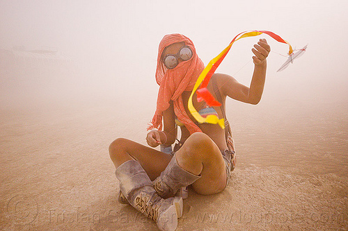 flying a mini kite, burning man, cross-legged, dust storm, flying, goggles, haboob, minah, mini kite, orange scarf, playa dust, sitting, streamer, string, whiteout, wind, woman