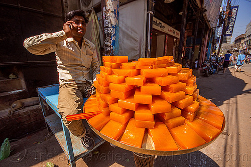 fruit jam street vendor (india), india, man, orange color, plate, selling, stacked, street food, street seller, varanasi, vendor