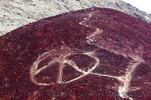 giant peace symbol stone graffiti, basalt, death valley, igneous rocks, men, peace symbol, saline valley, stone graffiti, trail, volcanic rocks, volcano