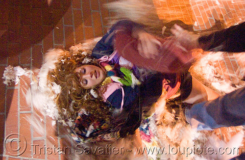 girl lying on the ground - the great san francisco pillow fight 2009, down feathers, night, pillows, woman, world pillow fight day