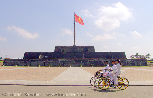 girls on bicycles - cot co flag tower (hué) - vietnam, bicycles, bikes, cot co, flagpole, hué, red flag, three, vietnam flag
