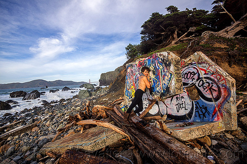 graffiti on concrete ruins, abandoned, concrete, driftwood, graffiti, ocean, rocks, ruins, sea, seashore, shore, tree logs, trees, water, woman, yassmine